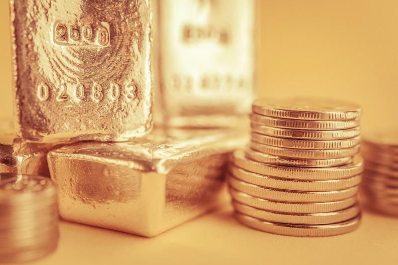 Odlewane sztabki złota i stos złotych monet bulionowych - GoldBroker.pl
